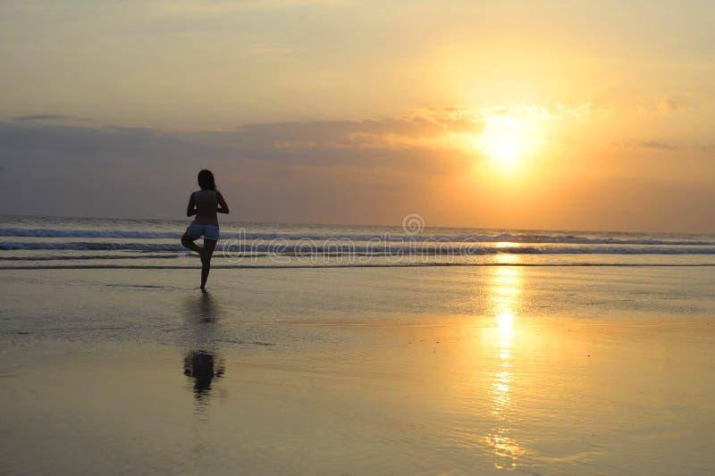 Kobieta medytuje pokojowo i myśleć w joga pozie na pustyni plaży na zmierzchu w medytaci i wolności zdjęcia stock