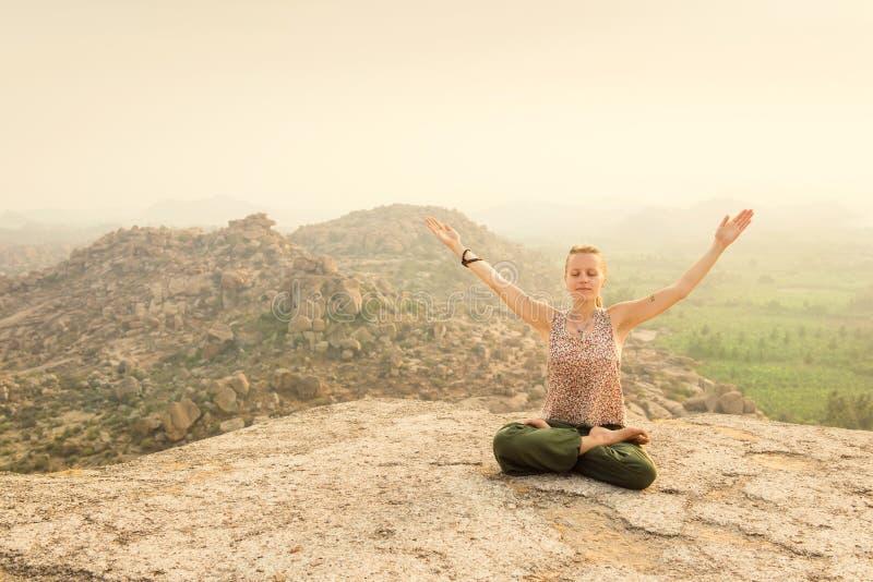Kobieta medytuje przy skalistą górą na wschodzie słońca, India zdjęcia royalty free
