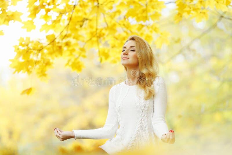 Kobieta medytuje w jesień parku fotografia stock
