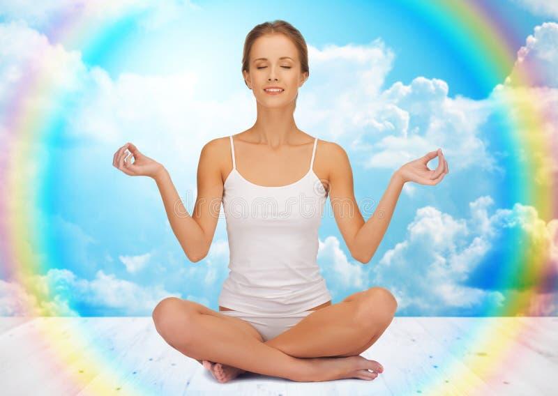 Kobieta medytuje w joga lotosu pozie zdjęcia royalty free