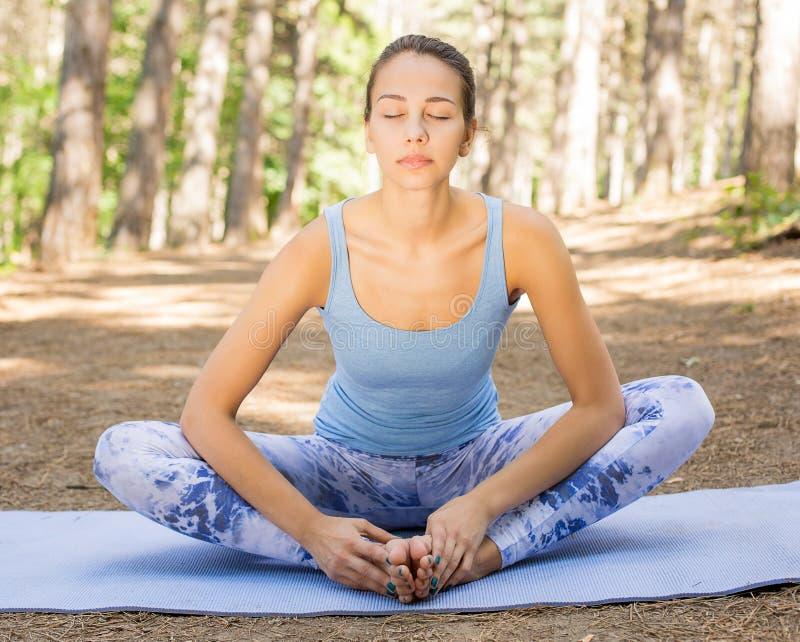 Kobieta medytuje z oczami zamykał rozciąganie robi joga outdoors w parku zdjęcia royalty free