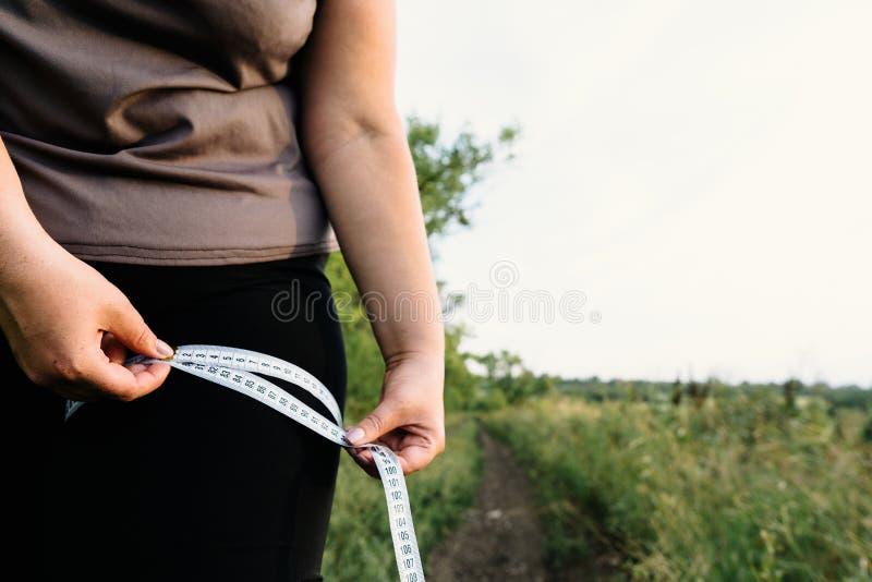 Kobieta mierzy jej udo z miarą taśmy fotografia stock