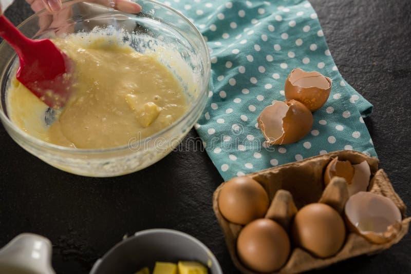Kobieta miesza ciasto naleśnikowe bici jajka, mleko i masło w pucharze, fotografia stock