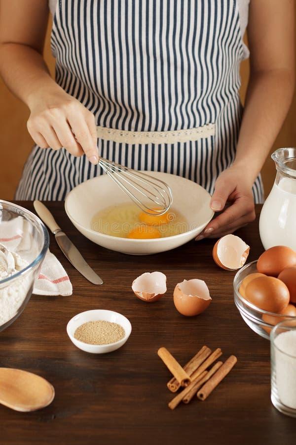 Kobieta miesza jajka w pucharze dla ciasto przepisu na kuchennym stole obraz stock