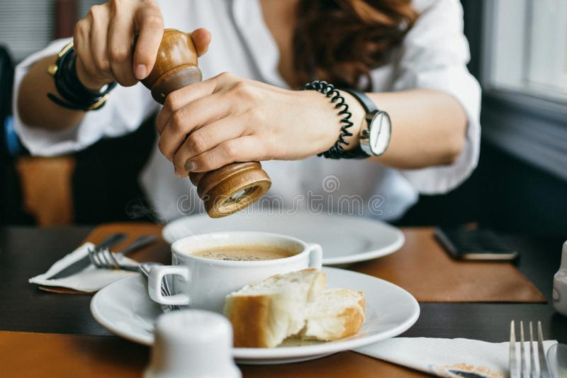 Kobieta mleje pieprzu filiżanka polewka, punkt ostrość obrazy royalty free