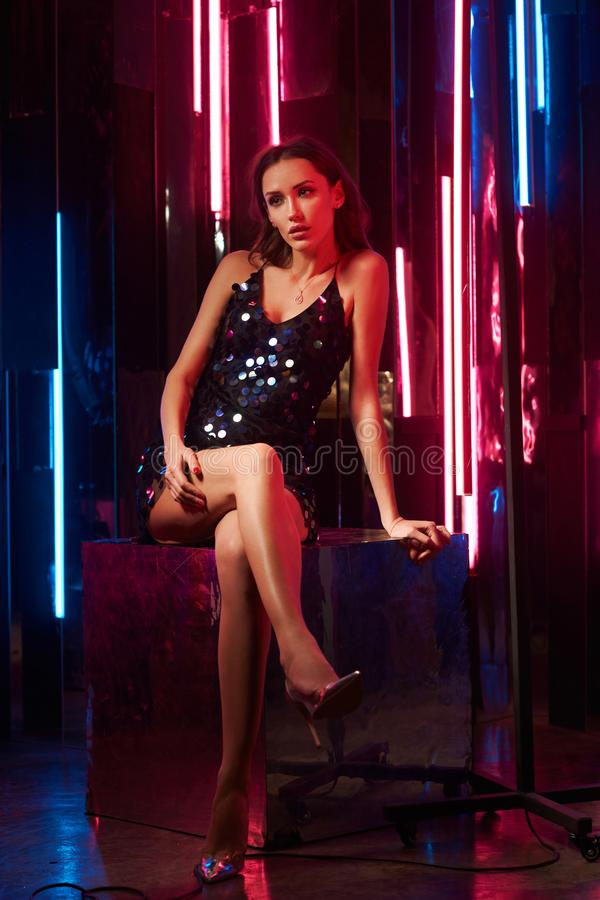 Kobieta model w czarnym błyszczącym cami sukni obsiadaniu na wielkim sześcianie i zdjęcia stock