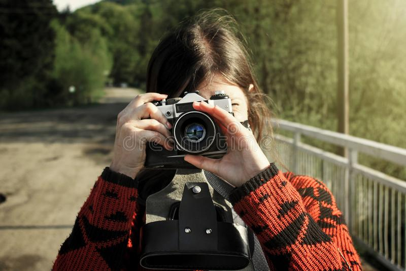 Kobieta modnisia podróżnik trzyma analogową fotografii kamerę w górach, obrazy royalty free