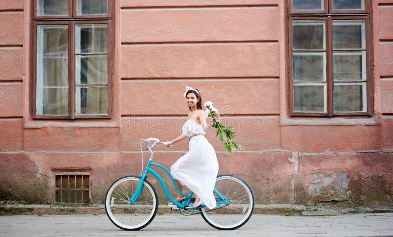 Kobieta na bicyklu jedzie wzdłuż starego miasta z peoniami obrazy stock