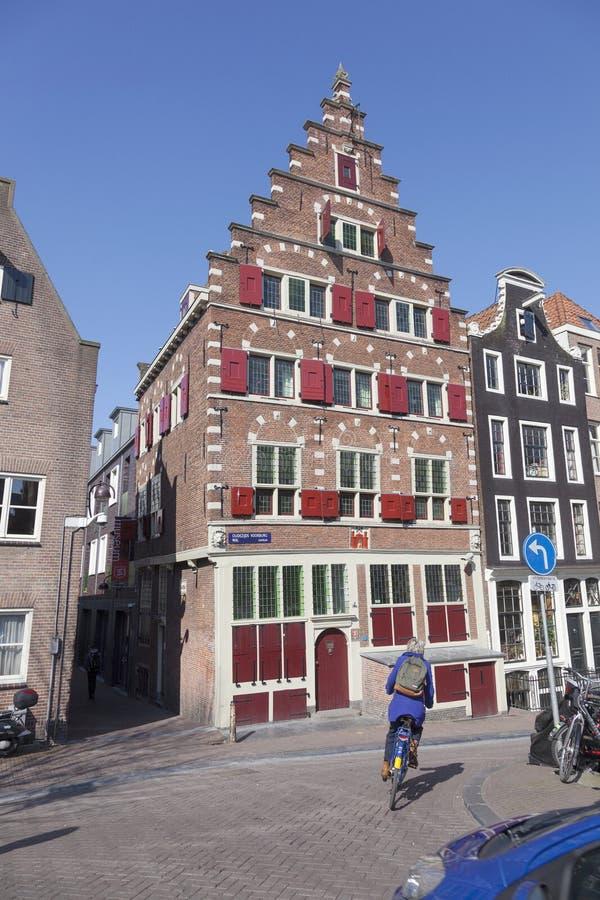Kobieta na bicyklu przechodzi starego dom w Amsterdam czerwonego światła okręgu obrazy stock