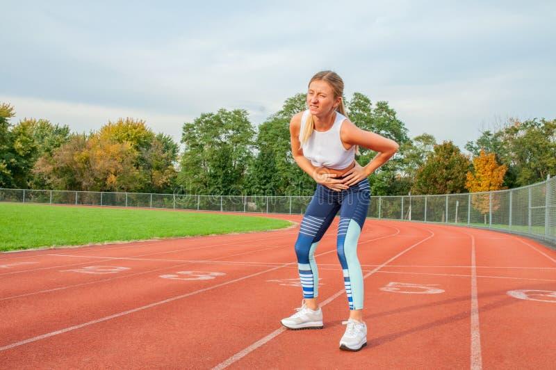 Kobieta na bieg śladzie bocznych drętwienia podczas treningu fotografia royalty free