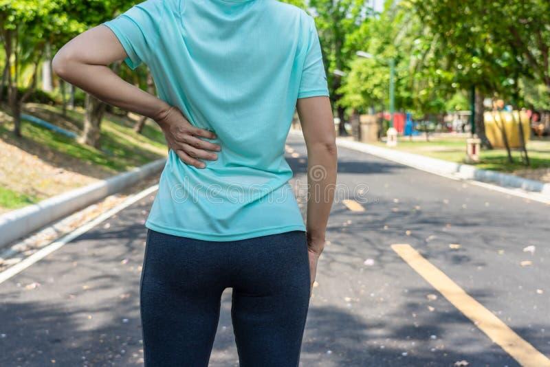 Kobieta na działającej drodze w parku ma ból pleców obraz royalty free