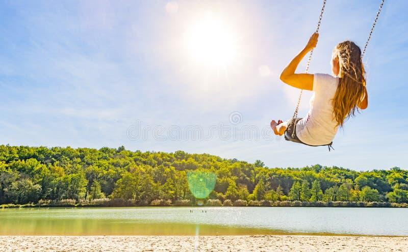 Kobieta na huśtawce przy jeziorem zdjęcie royalty free