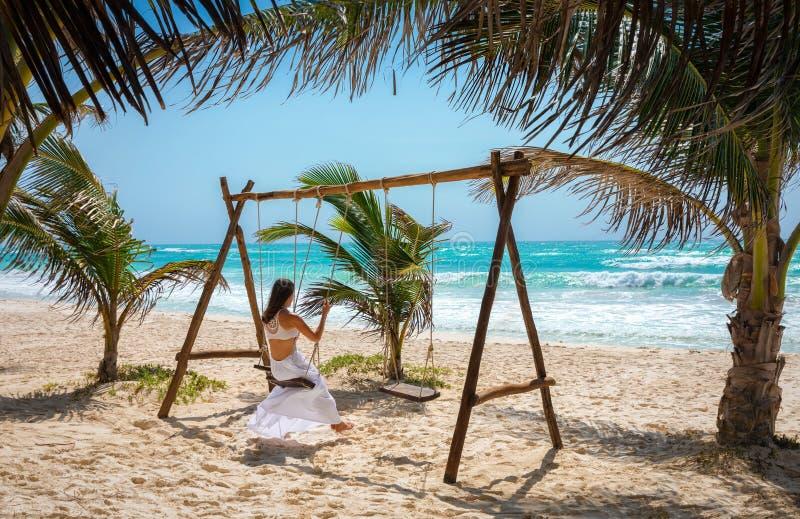 Kobieta na huśtawce na tropikalnej plaży Tulum zdjęcia royalty free