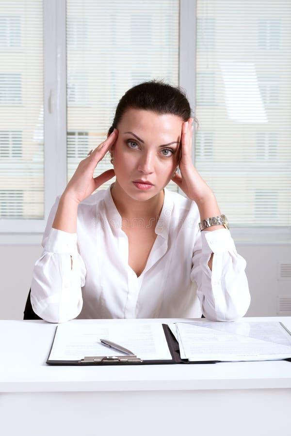 Kobieta na miejsce pracy głowie dotyka ona ręki ponieważ a obraz royalty free