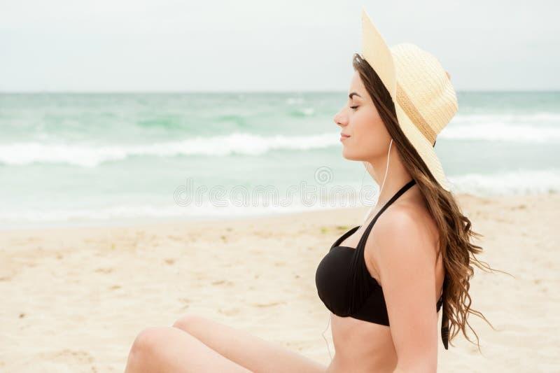 Kobieta na plażowym słuchaniu jej głowa telefony zdjęcia stock