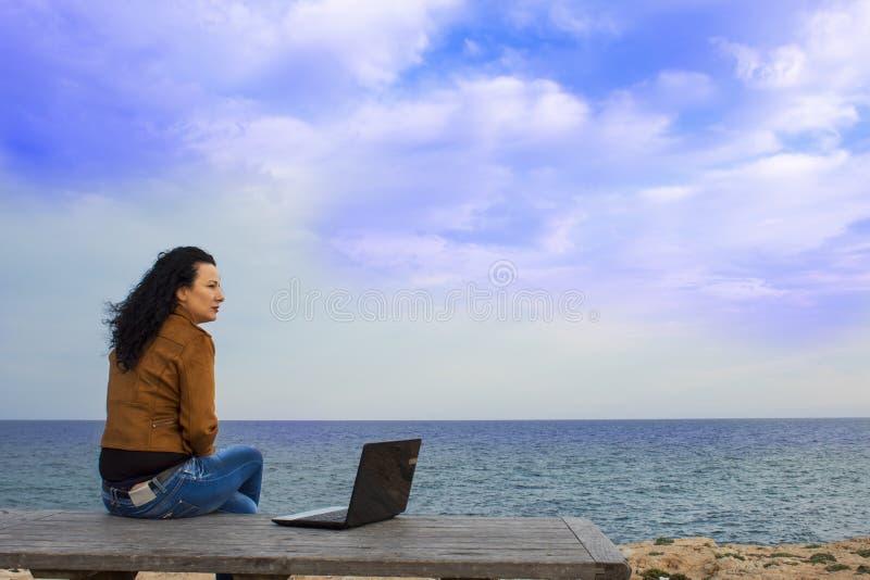 Kobieta na plaży Młoda kobieta przeciw morzu z komputerem fotografia stock