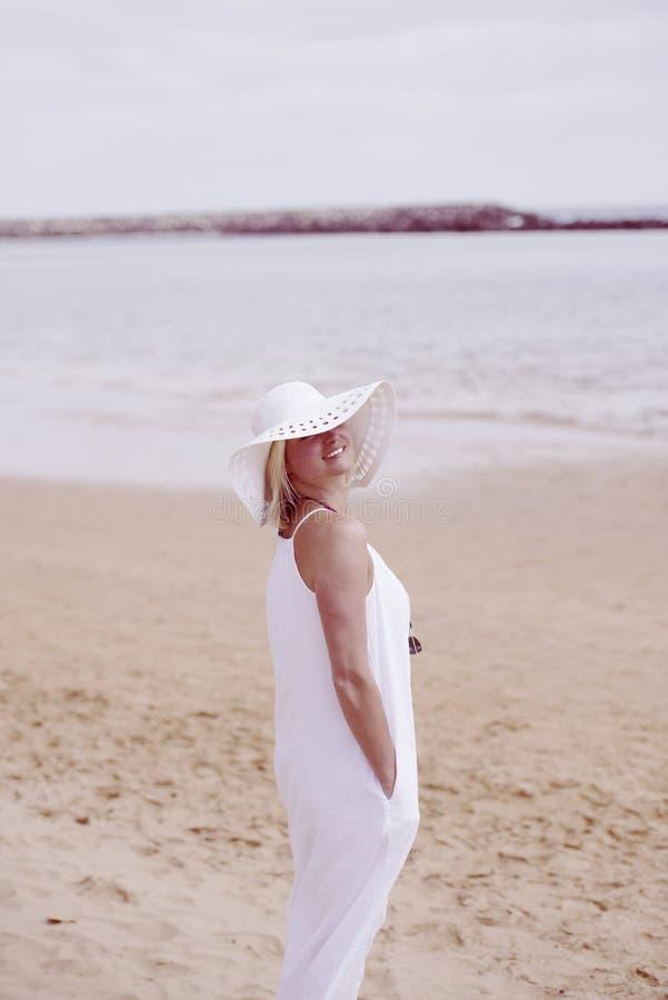 Kobieta na plaży w bielu kapeluszu i sukni fotografia royalty free