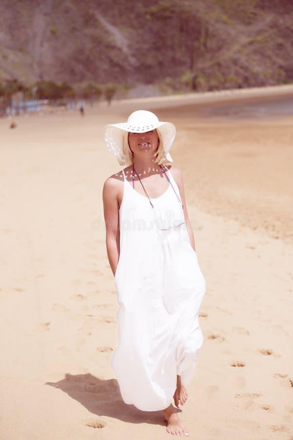 Kobieta na plaży w bielu kapeluszu i sukni zdjęcie royalty free