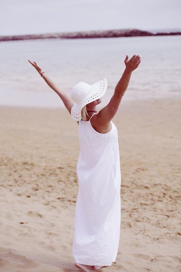 Kobieta na plaży w bielu kapeluszu i sukni obrazy stock