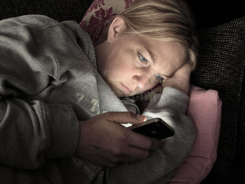 Kobieta na smartphone w zmroku samotnie obraz royalty free