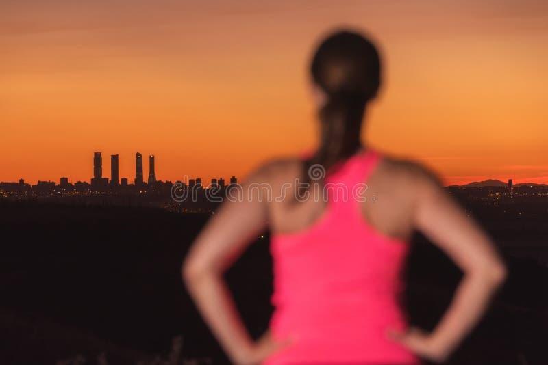 Kobieta na sporta dopatrywania odzieżowym zmierzchu nad miasto linią horyzontu Ostrość jest na tle fotografia royalty free