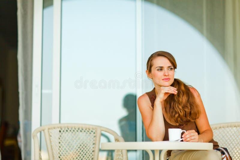 Kobieta na tarasowym mieć filiżankę kawy zdjęcie stock