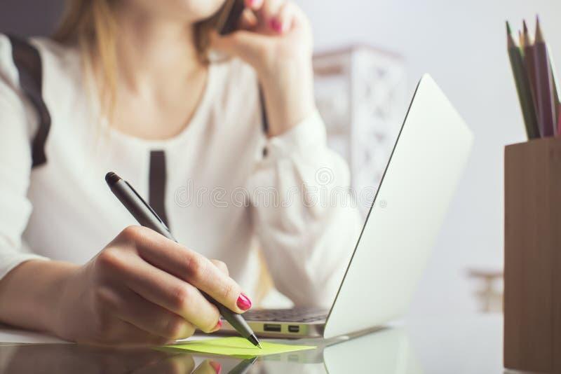 Kobieta na telefonu writing notatce zdjęcie royalty free