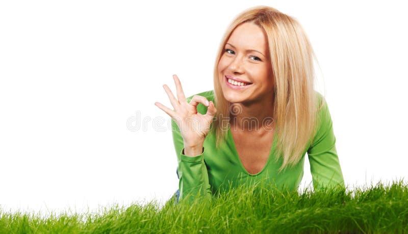 Kobieta na trawy przedstawienia OK obraz royalty free
