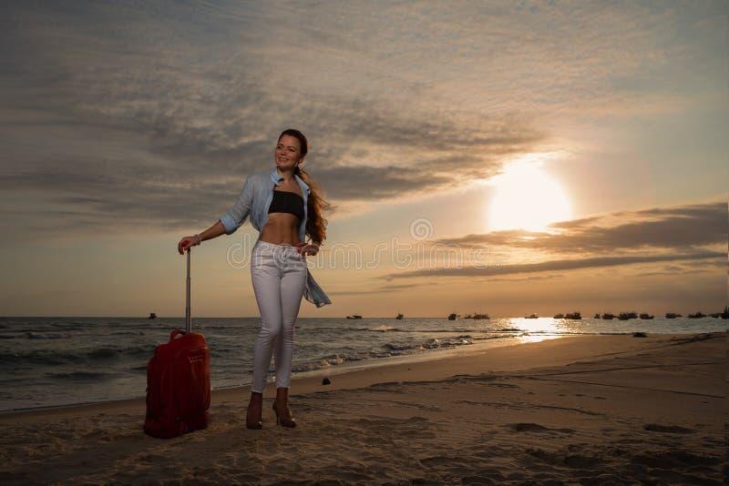 Kobieta na tropikalnym beachin kapeluszu z wielką czerwoną walizką obrazy stock