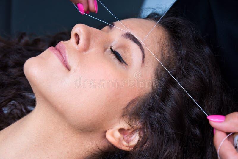 Kobieta na twarzowego włosy usunięciu threading procedurę obrazy royalty free