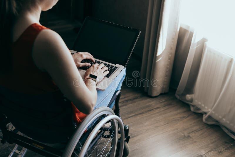 Kobieta na wózku inwalidzkim w domu z laptopem na kolanach, dłoń blisko, nierozpoznawalny mężczyzna obraz stock