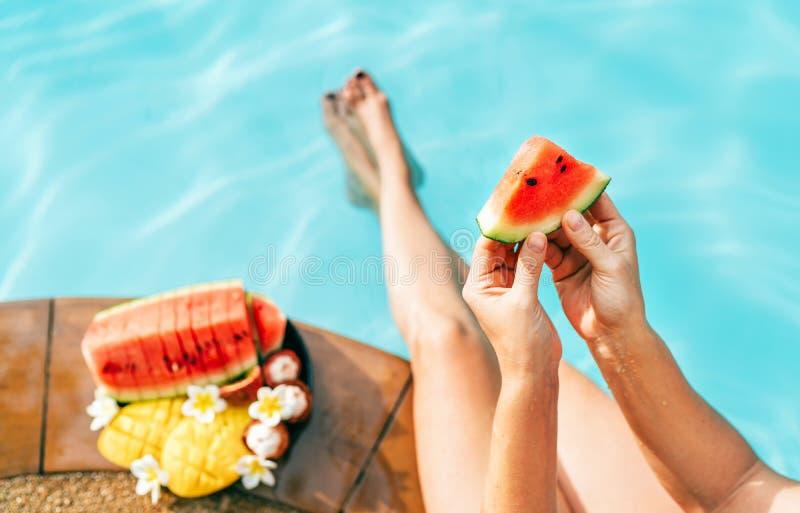 Kobieta nabiera ręki mały arbuza kawałek, siedzi na basen krawędzi enjoing świeżych owoc i zdjęcia stock