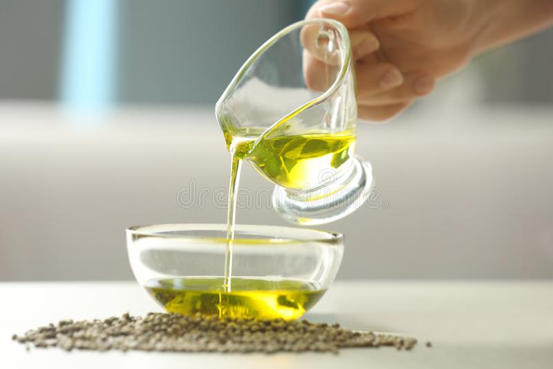 Kobieta nalewa konopianego olej w szklanym pucharze zdjęcie stock