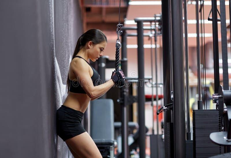 Kobieta napina ręka mięśnie na kablowej maszynie w gym obraz stock