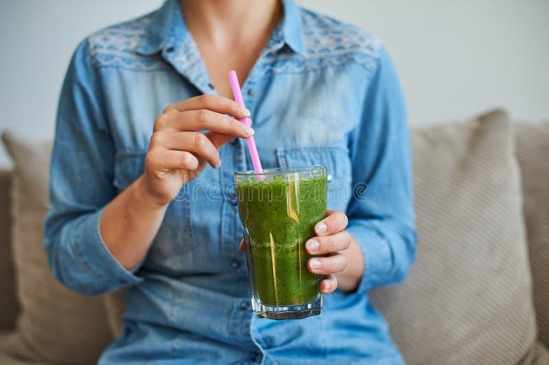 Kobieta napoju healty smoothie z zielonymi warzywami zdjęcia royalty free