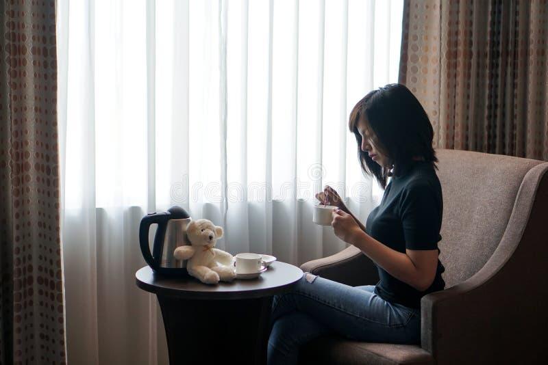 Kobieta napoju kawa w pokoju hotelowym okno obrazy royalty free