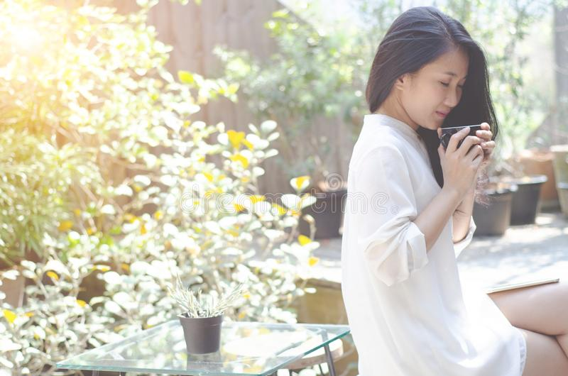 Kobieta napoju kawa w ranku ogr?dzie zdjęcia royalty free