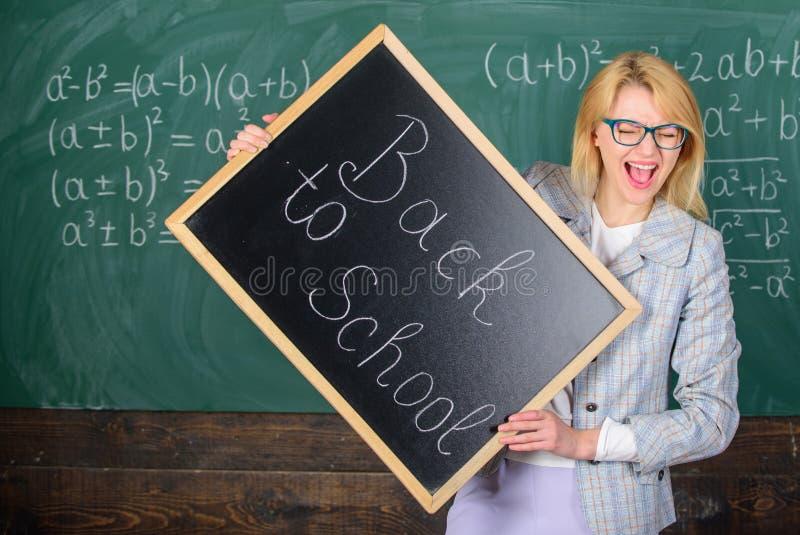 Kobieta nauczyciel trzyma blackboard inskrypcję z powrotem szkoła Zatrudniać nauczycieli dla nowego roku szkolnego Patrzeć popełn obraz stock