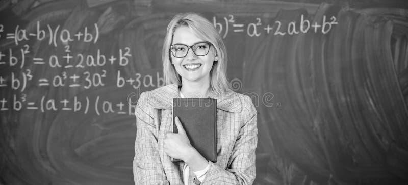 Kobieta nauczyciel z ksi??k? przed chalkboard my?l? o pracie Poznawanie proces w uczenie Poznawanie proces obraz stock