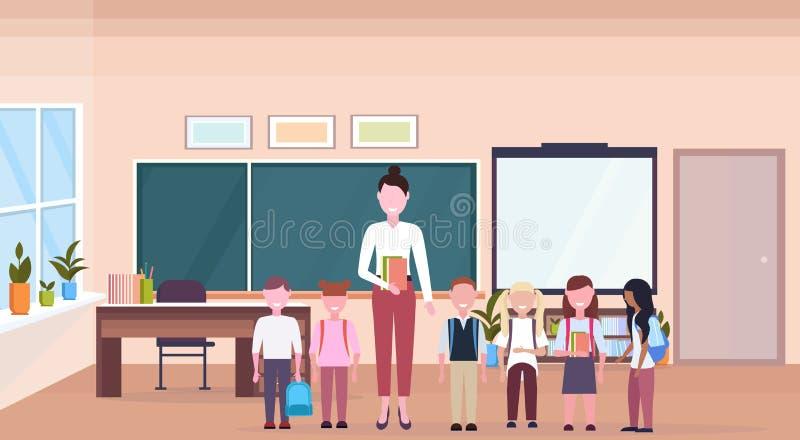 Kobieta nauczyciel z mieszanki rasy uczniami stoi w nowożytnej szkolnej sali lekcyjnej kredowej deski biurka wewnętrznych postaci ilustracja wektor