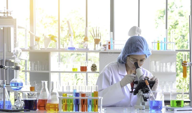 Kobieta naukowiec robi eksperymentowi z mikroskopem obraz stock