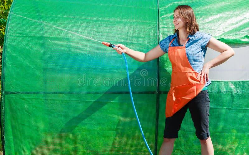 Kobieta nawadnia ogród z wężem elastycznym obraz stock