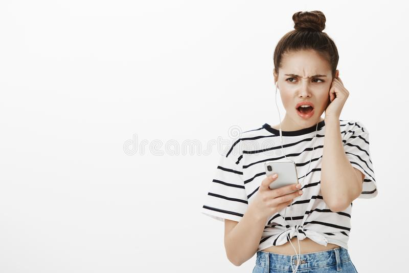 Kobieta nierada przesłuchanie piosenka no lubi Portret nieszczęśliwy rozczarowany żeński uczeń z babeczki fryzurą zdjęcie stock