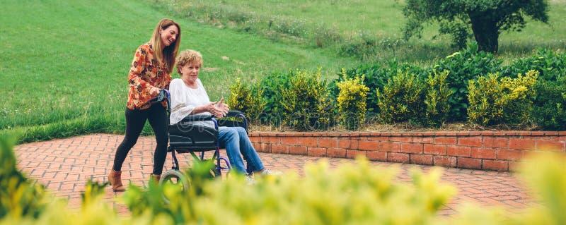Kobieta niesie jej matki w wózku inwalidzkim obraz stock
