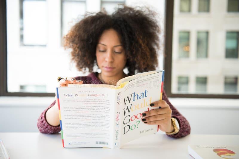 Kobieta nosząca kasztanową koszulkę z długimi rękami czytająca co zrobiłaby Google obrazy royalty free