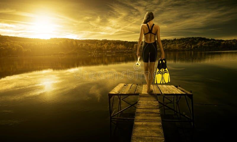 Kobieta nurek w swimsuit, na krawędzi mola fotografia stock