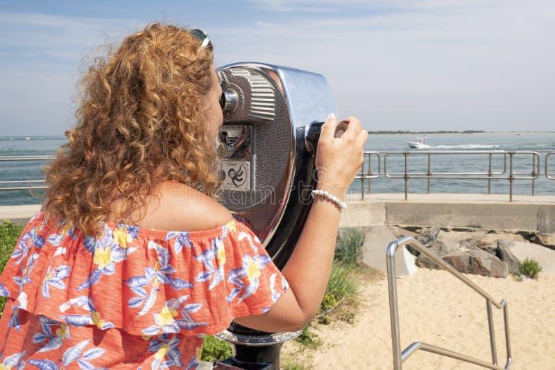Kobieta obserwuje przez moneta działający obuocznego obraz royalty free