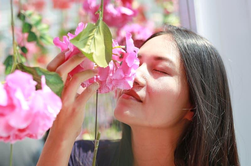 Kobieta obwąchuje kwiaty na słonecznym dniu Otacza kwiecenie zdjęcie stock