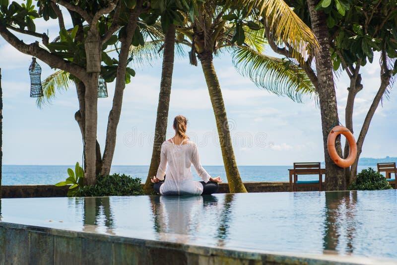 Kobieta od plecy w sporta kostiumu siedzi w lotosowej pozie, medytuje na krawędzi basenu na wybrzeżu ocean w tropikalnym fotografia royalty free