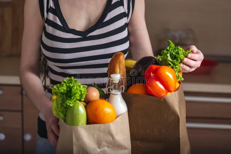 Kobieta odpakowywa pełną papierową torbę z produktami na tle kuchnia Zdrowa żywność organiczna dla zrównoważonej diety obraz royalty free